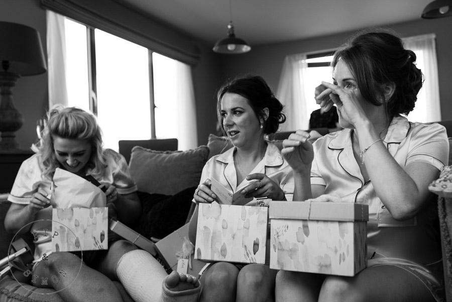 Emotional bridesmaids together opening gifts.