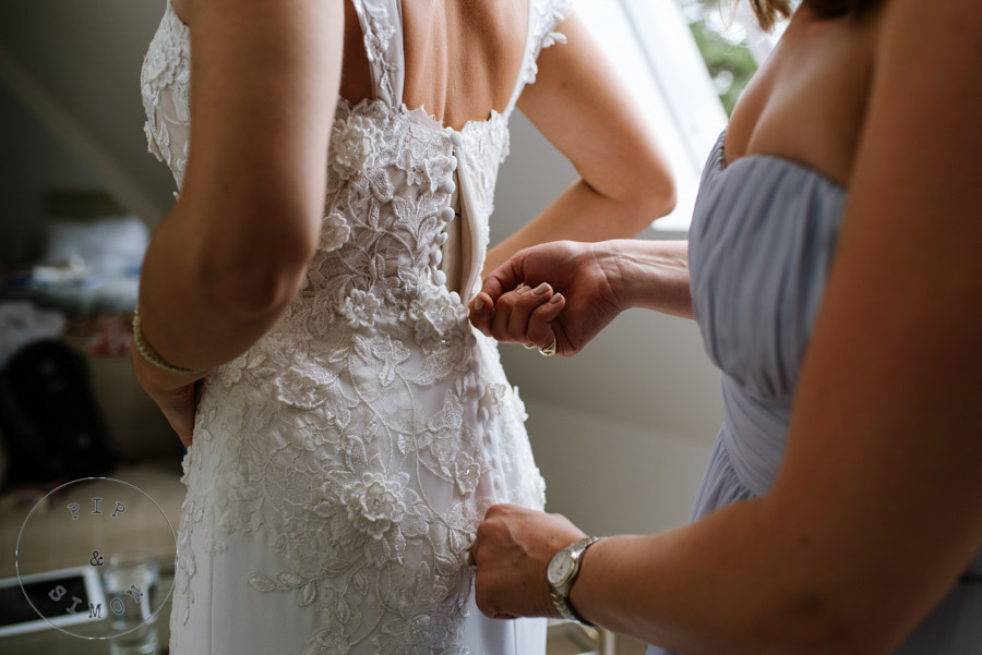 A bridesmaid helps a bride with her dress.