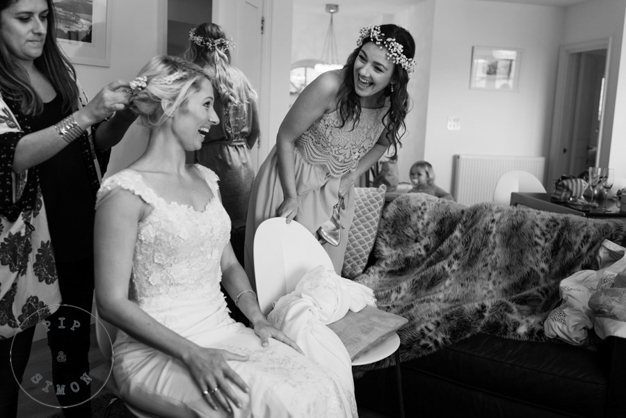 Bridesmaids laugh with the bride as they get ready.