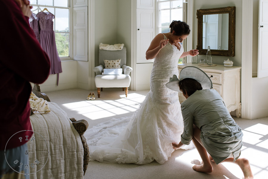 A bride's mother helps her with her dress.