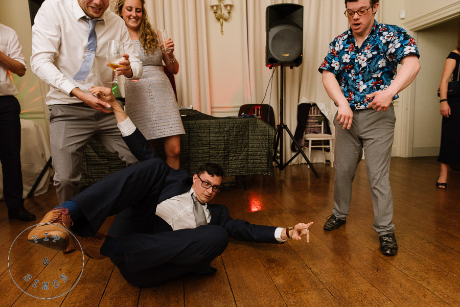 Lively wedding guests dance at an evening reception.
