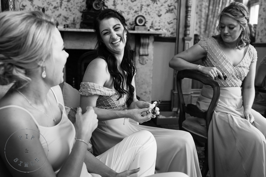 Bride laughs with bridesmaids on the morning of her wedding.