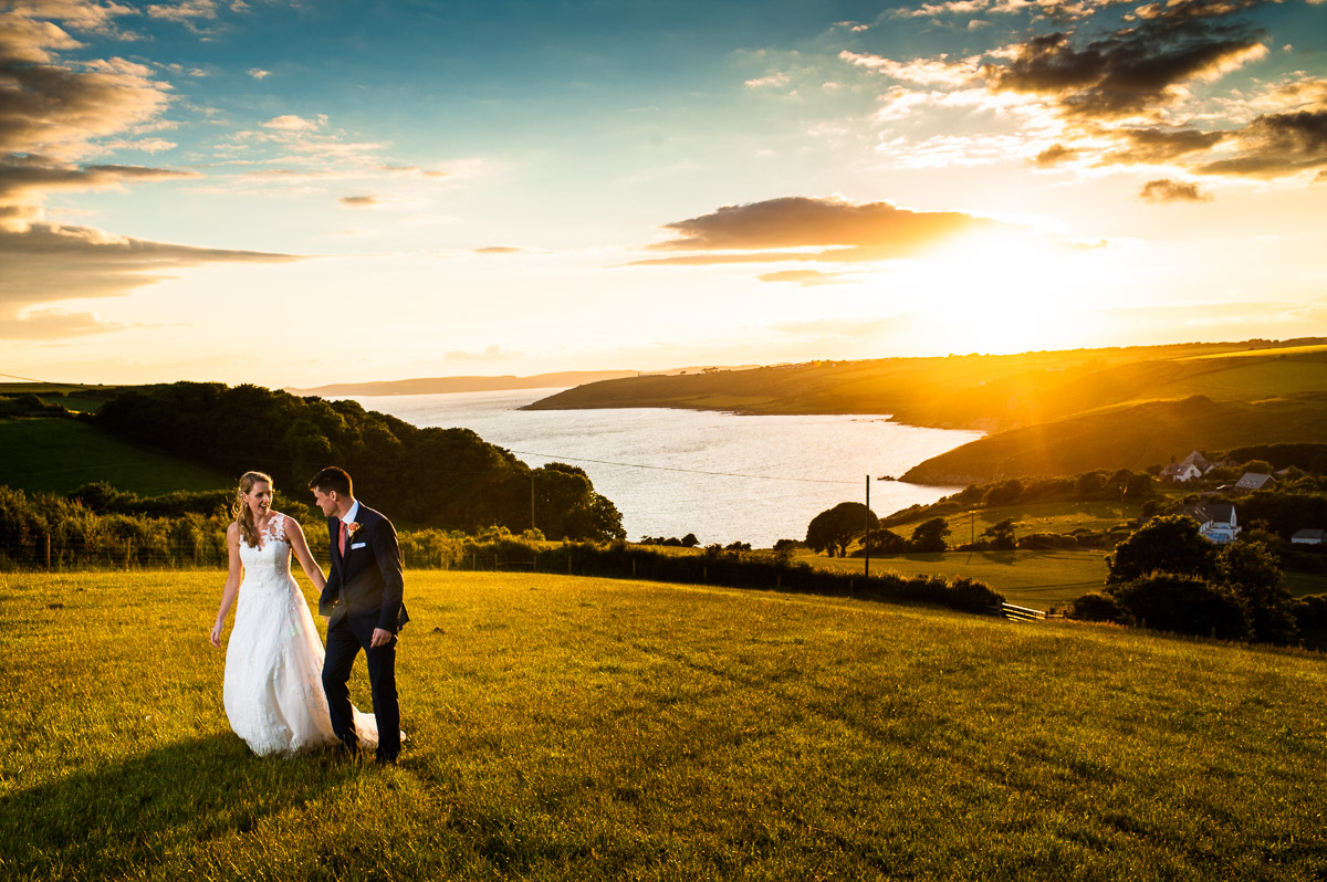 A stunning sunset over the sea as Bride and Groom walk in the South Devon countryside during their wedding.