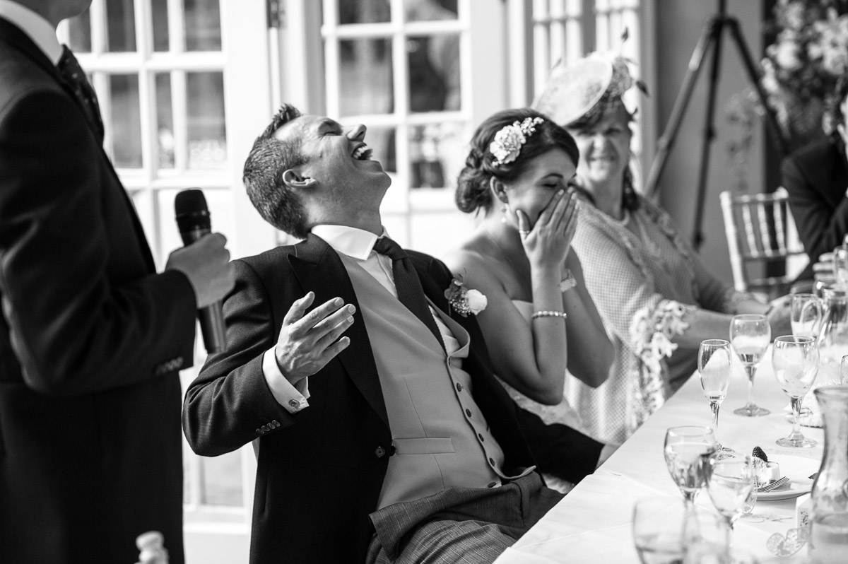 Groom laughs during the speeches at his wedding in Devon.