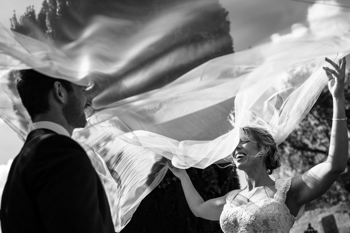 Laughing Bride throwing her veil in the air, covering the Groom's head.