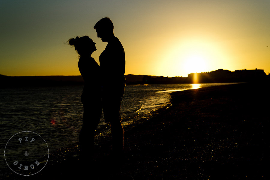 A silhouette of a couple with a warm sunset behind them.