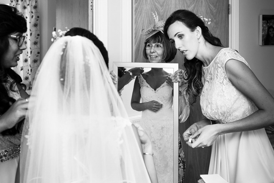 A Bride's mother holds a mirror as the Bride gets ready.