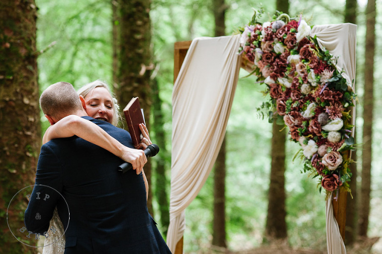 A bride and groom embrace during their woodland wedding at Buckland House.