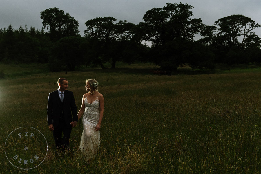 A wedding couple walk in a field at night