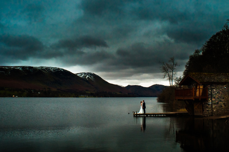 Photography of a wedding couple talking on a jetty with lakes and mountains behind them.