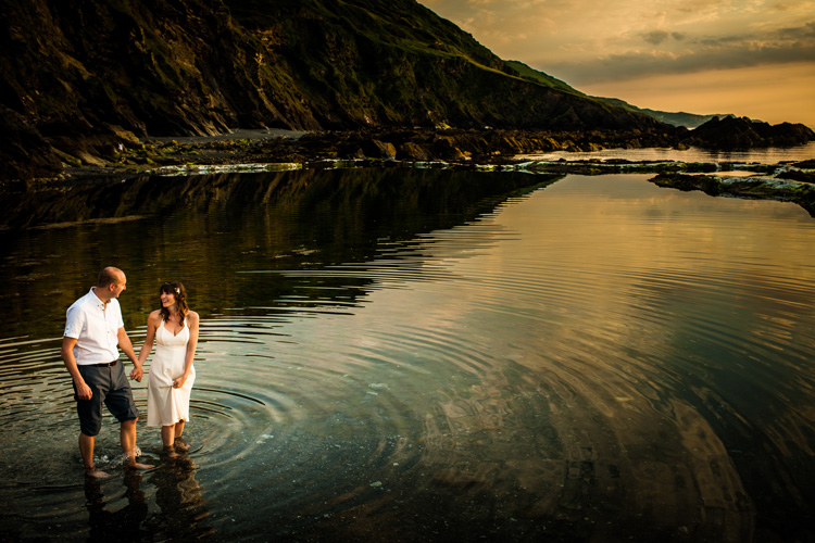 A bride and groom walk through a tidal pool at sunset.