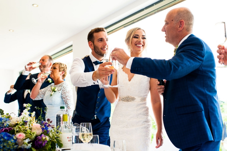 Bride and Groom during wedding speech toasts by Somerset Wedding Photographers Pip and Simon.