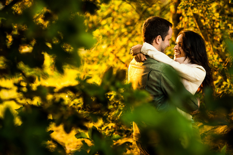 A couple talking together in a woodland setting at sunset.