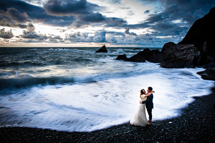 A couple hug on a beach with a dramatic sky.