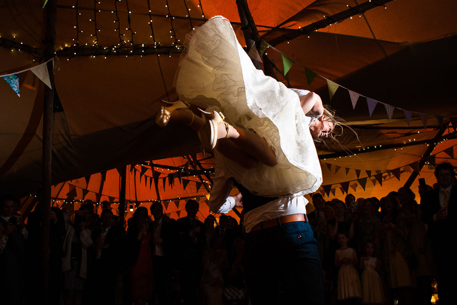 A bride being carried in the air, by her groom, during their first dance.
